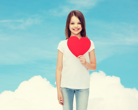 love, charity, childhood and people concept - beautiful little girl sitting at table and holding red heart cutout over blue sky background