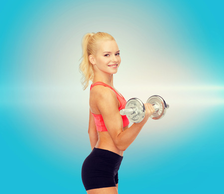 musculine: fitness, healthcare and exercise concept - young sporty woman with heavy steel dumbbell