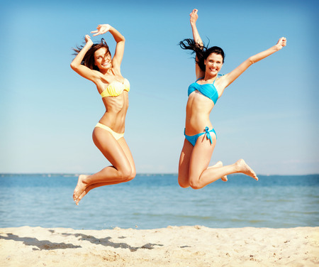 summer holidays and vacation concept - beautiful girls in bikini jumping on the beach