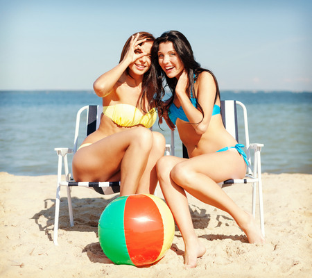 teen beach: summer holidays and vacation - girls in bikinis sunbathing on the beach chairs Stock Photo