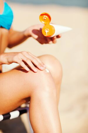 suncare: summer holidays and vacation - girl putting sun protection cream on the beach chair