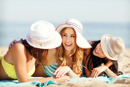 laughing girl: summer holidays and vacation - girls in bikinis sunbathing on the beach