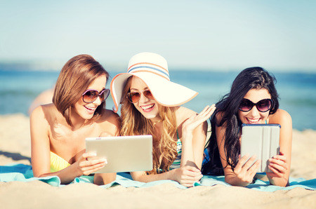 e reading: summer holidays, technology and internet concept - girls in bikinis with tablet pc sunbathing on the beach