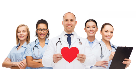 medicine, profession, teamwork and healthcare concept - international group of smiling medics or doctors with clipboard and stethoscopes holding red paper heart shape over white background photo