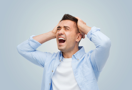 desperation: stress, headache, desperation, grief and people concept - unhappy man with touching his head and screaming over gray background Stock Photo