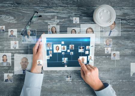 comunicación: negocio, la gente, la comunicación internacional, headhunting y tecnología concepto - cerca de las manos apuntando el dedo a la pantalla del ordenador Tablet PC con la red mapa del mundo e internet contactos en la mesa