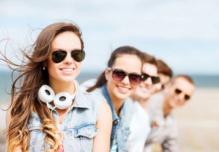 happy teenagers: summer holidays and teenage concept - teenage girl with friends outside