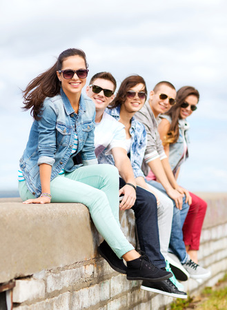 chill out: summer holidays and teenage concept - group of teenagers hanging out outside