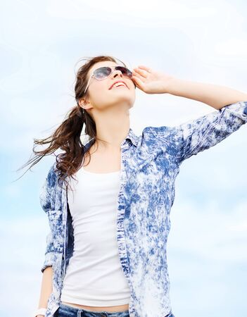 ourdoor: summer holidays and teenage concept - teenage girl in shades outside Stock Photo