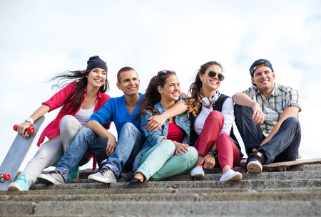 school friends: summer holidays and teenage concept - group of teenagers with skates outside Stock Photo