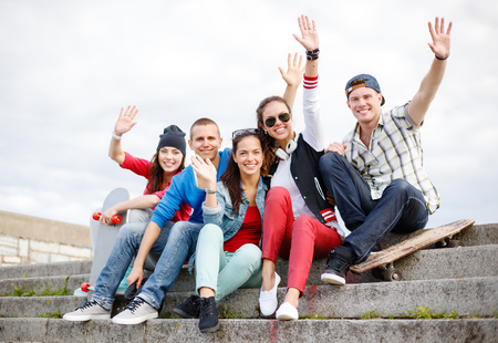 summer holidays and teenage concept - group of smiling teenagers hanging outside and waving hands Foto de archivo