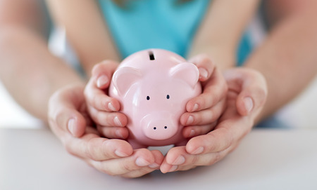 family, children, money, investments and people concept - close up of father and daughter hands holding pink piggy bank Standard-Bild
