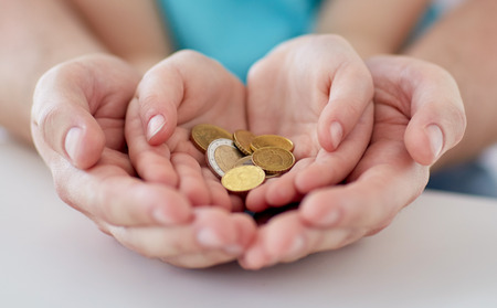 family, children, money, investments and people concept - close up of father and daughter hands holding euro money coins