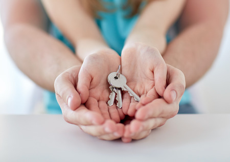 key: people, charity, family, real estate and home concept - close up of man and girl holding house keys in cupped hands