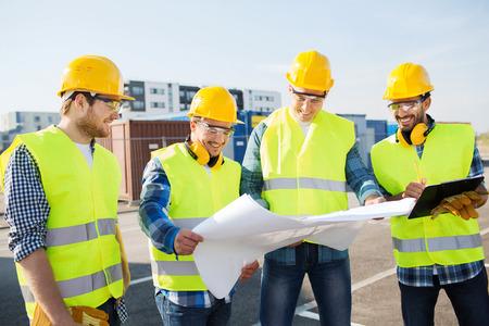 worker: negocio, construcción, trabajo en equipo y concepto de la gente - grupo de sonrientes constructores de cascos con el portapapeles y modelo al aire libre Foto de archivo