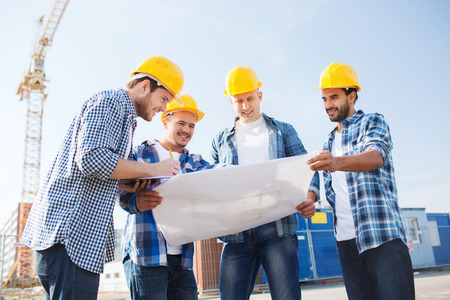 sites: business, building, teamwork and people concept - group of smiling builders in hardhats with clipboard and blueprint outdoors