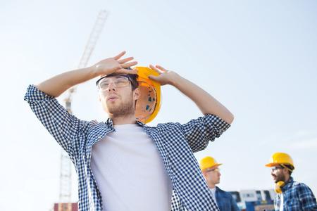 sudoracion: negocio, construcción, trabajo en equipo y concepto de la gente - grupo de constructores de cascos al aire libre
