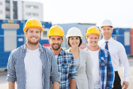 obrero trabajando: negocio, construcción, trabajo en equipo y concepto de la gente - grupo de sonrientes constructores de cascos al aire libre Foto de archivo