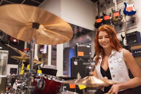 cymbals: music, sale, people, musical instruments and entertainment concept - smiling female musician playing cymbals at music store