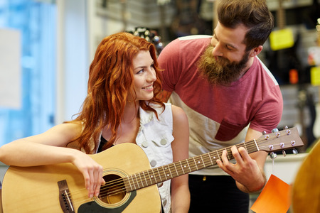 teaching music: music, sale, people, musical instruments and entertainment concept - happy couple of musicians with guitar at music store