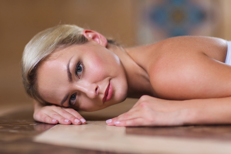 turkish bath: people, beauty, spa, healthy lifestyle and relaxation concept - beautiful young woman lying on hammam table in turkish bath Stock Photo