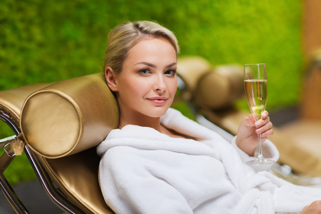 people, beauty, lifestyle, holidays and relaxation concept - beautiful young woman in white bath robe lying on chaise-longue and drinking champagne at spa