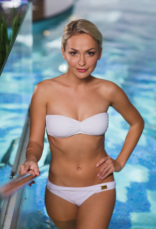 upstairs: people, beauty, spa, healthy lifestyle and relaxation concept - beautiful young woman in bikini swimsuit raising upstairs in swimming pool