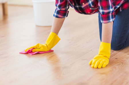 floor cloth: people, housework and housekeeping concept - close up of woman in rubber gloves with cloth cleaning floor at home Stock Photo