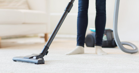 people, housework and housekeeping concept - close up of woman with legs vacuum cleaner cleaning carpet at home Stock Photo