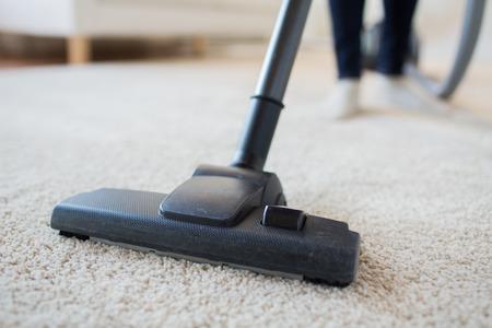 orden y limpieza: las personas, el trabajo doméstico y de limpieza concepto - cerca de la mujer con las piernas aspiradora limpieza de alfombras en casa Foto de archivo