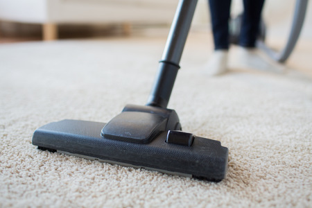 people, housework and housekeeping concept - close up of woman with legs vacuum cleaner cleaning carpet at home Stockfoto