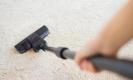 mujer limpiando: las personas, el trabajo dom�stico y de limpieza concepto - cerca de la mano con el aspirador de limpieza de alfombras en casa Foto de archivo