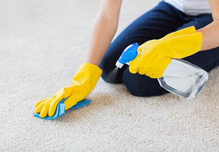 gospodarstwo domowe: ludzi, pracy w domu i sprzątanie koncepcji - zamknąć kobiety w gumowe rękawice z tkaniny i natrysku detergentu do czyszczenia dywanów w domu