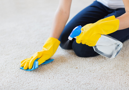 clean carpet: people, housework and housekeeping concept - close up of woman in rubber gloves with cloth and detergent spray cleaning carpet at home