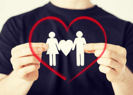 family and relationships concept - man hands showing two paper men with heart shape Stock Photo