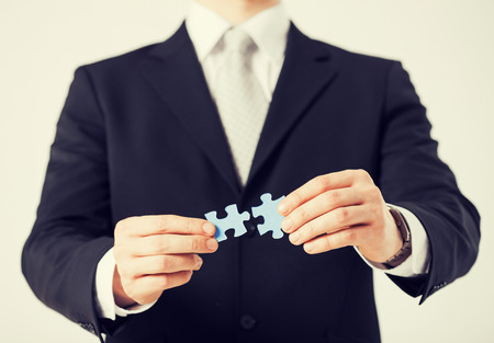 close up of man trying to connect puzzle pieces. photo