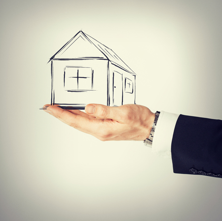 accommodation broker: real estate, technology and accomodation concept - picture of house on virtual screen in man hand Stock Photo