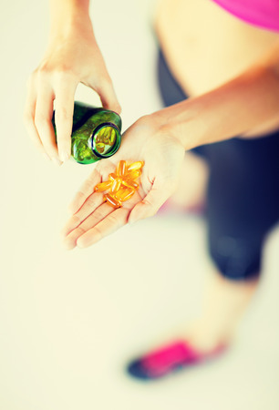 omega 3: sport and diet concept - woman hand with medication