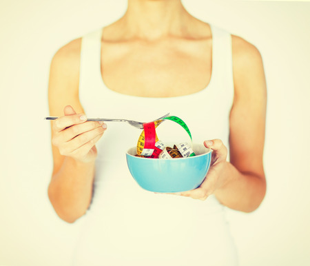 low calories: sport and diet concept - woman hands holding bowl with measuring tape Stock Photo