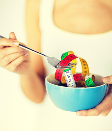 fat burning: sport and diet concept - woman hands holding bowl with measuring tape Stock Photo