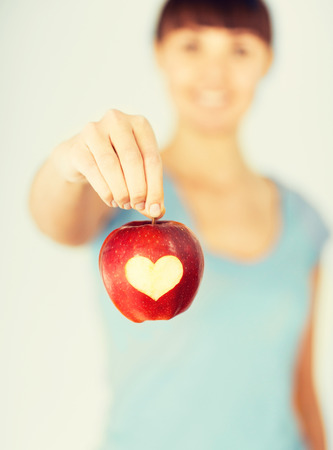 digestion: healthy food and lifestyle - woman hand holding red apple with heart shape
