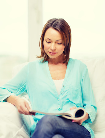 home and leasure concept - smiling woman reading magazine at home Stock Photo