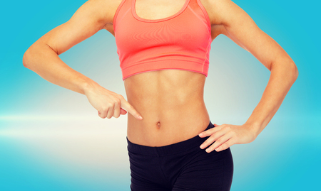 stamina: fitness, exercise and diet concept - close up of woman pointing finger at her six pack Stock Photo