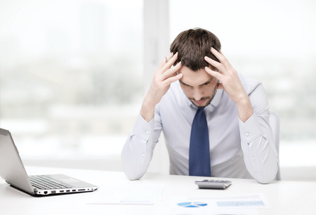 office, business, technology, finances and internet concept - stressed businessman with laptop computer and documents at office Stockfoto