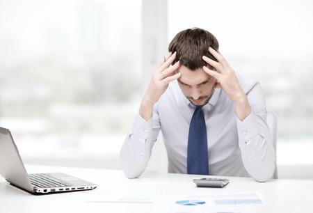 office, business, technologie, financiën en internet concept - beklemtoonde zakenman met laptop en documenten op het kantoor