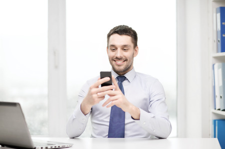 businessman: business, office and technology concept - smiling businessman with laptop computer and smartphone at office