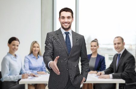 welcome people: business and office concept - handsome businessman with open hand ready for handshake Stock Photo