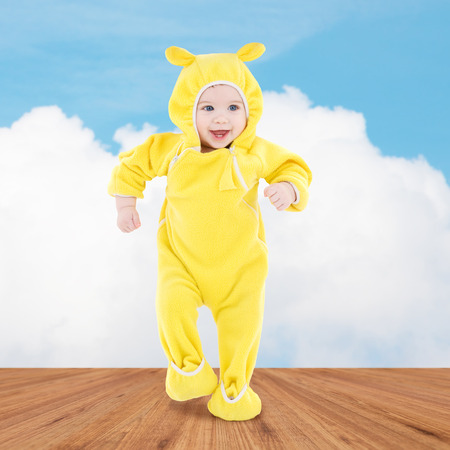 rompers: people, children, achievement and happiness concept - happy baby in yellow suit making first steps over wooden floor and blue sky background