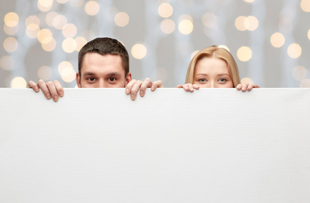 big behind: people, advertisement and information concept - happy couple hiding behind big white blank board over holidays lights background Stock Photo