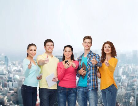 the girl is young: friendship, technology, gesture and people concept - group of smiling teenagers with smartphones and tablet pc computers showing thumbs up over city background